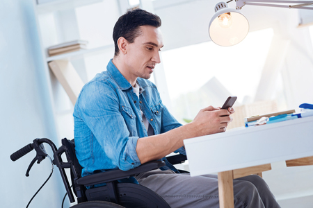 Solo atención. Hombre serio que se sienta en la silla de ruedas y que inclina la cabeza mientras que mira el teléfono Foto de archivo