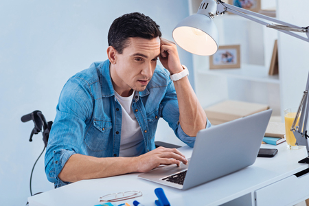 Let me think. Serious man wrinkling forehead and looking at computer while leaning elbows on table Stock Photo