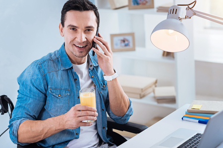 Pause at work. Cheerful invalid sitting in his wheelchair and holding glass with juice while talking per telephone Stock Photo