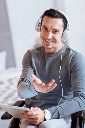 It is for you. Cheerful man expressing positivity while looking at camera and listening music