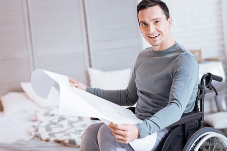 Staring you. Delighted man expressing positivity and looking forward while sitting in semi position Stock Photo