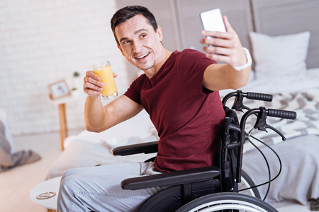 Fresh juice. Kind male wrinkling forehead and keeping smile on his face while sitting on the wheelchair