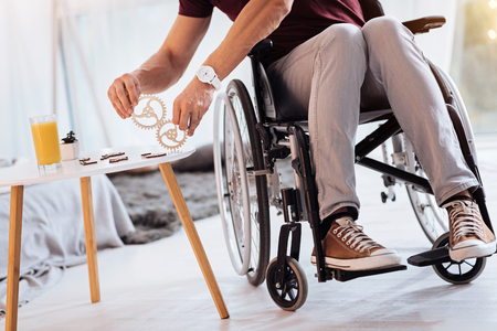 Two details. Disabled male person holding wooden parts in both hands and sitting on the wheelchair while being at home Stock Photo
