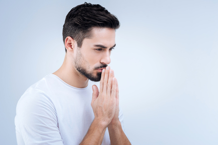 Praying. Unhappy calm young man finding inner peace and harmony while standing with his hands closed and praying