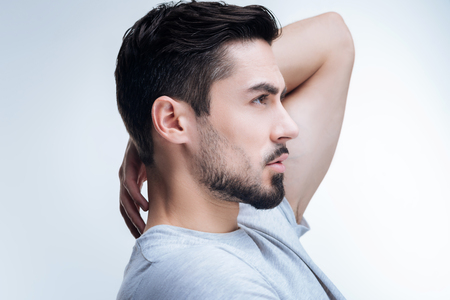 boasting: New haircut. Handsome fashionable young man standing against the blue background with his hand on his neck while boasting his new haircut Stock Photo