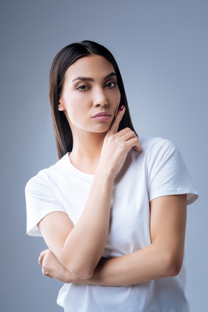 Too strict. Beautiful serious professional manager standing against the blue background with her finger up near her face while looking into the distance and expressive no positive emotions Stock Photo