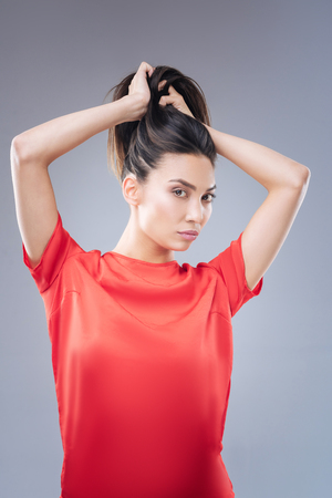 Lovely hairstyle. Fashionable young beautiful woman standing in front of the mirror and trying to make a pretty ponytail