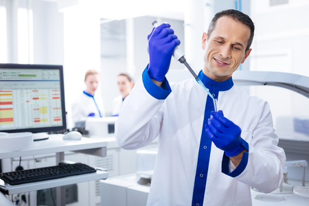 Satisfied with results. Budding cheerful male laboratorian  smiling to himself looking at the vial while holding it Stock Photo