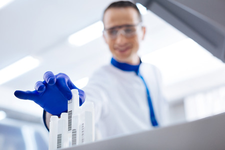 Preparation in action. Smiling serious male laboratorian who wearing blue gloves preparing for FBS by pulling out the transparent  container Stock Photo