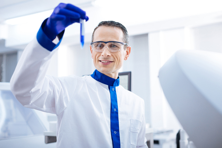 Lets see. Joyfull  determined male researcher jiggling test tube with blue liquid while examining it and standing in the lab Stock Photo