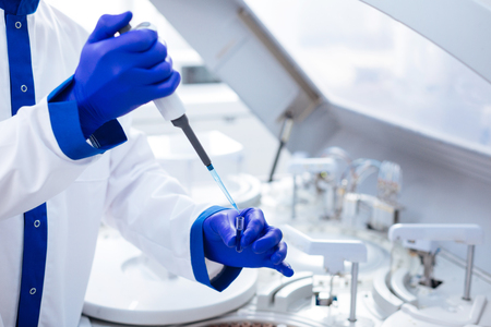 Precise level. Pipette dropping reagent in the glassware while placed in the hands and located in the lab