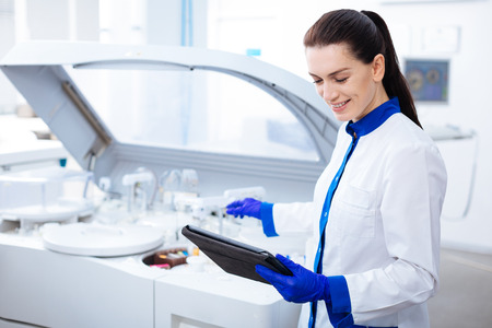 Science is light. Beautiful gentle inspired  female intern smiling adorably and looking at the tablet while stretching her hand to the centrifuge machine Stock Photo