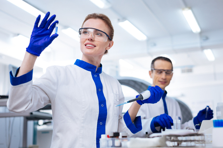 Biochemical lab. Glad inspired female lab assistant waiting for reaction after putting reagent into the sample with a pipette while wearing medical glasses
