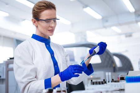 Caution with chemicals. Blond attractive female scientist   looking down and  holding pipette when posing against blurred background