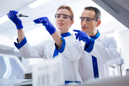 Perfect measurement. Two promising  cheerful researchers  wearing medical glasses while she holding pipette and test tube and he pointing at them