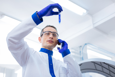 No answer. Thoughtful appealing male researcher asking for advice while holding test tube and examining it carefully Stock Photo
