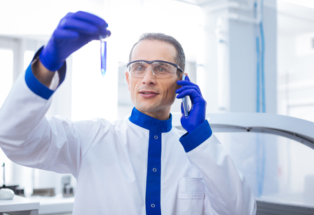 Phone conversation. Optimistic sweet male scientist talking on the phone while bringing up test tube with poured blue reagent