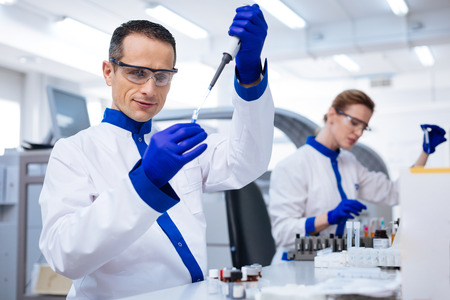 Routine test. Inspired prominent male laboratory assistant holding the glassware and dropping reagent there while wearing medical glasses