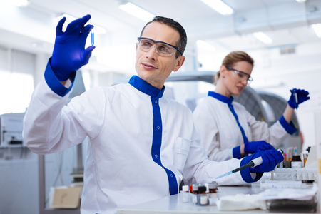 Advanced medication.  Kind budding male scientist placing the hand with pipette on the table and holding up the medication sample while wearing lab coat Stock Photo