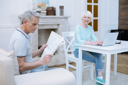 Interesting newspaper. Serious attentive old man looking concentrated while reading a newspaper with his wife sitting at the table