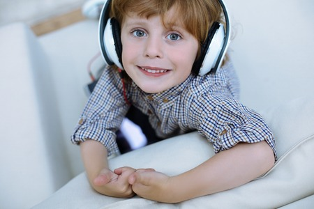 Cute boy. Pretty little smiling boy looking happy while listening to music in his headphones Stock Photo