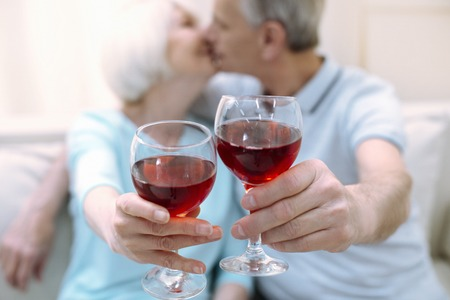 Romantic atmosphere. Two active romantic cute pensioners kissing while holding their drinks