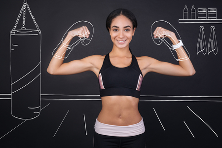 boasting: Stay fit and healthy. Cheerful delighted sporty woman boasting with her muscles and smiling while enjoying box training