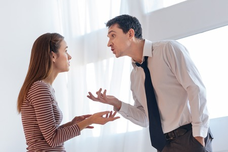 Misunderstanding. Emotional angry irritated man looking expressive while explaining his point of view to his upset wife