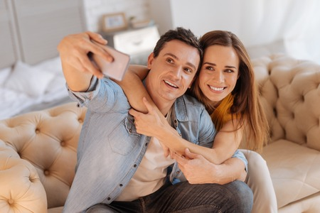 Nice photo. Cheerful beautiful loving people sitting together on a comfortable sofa and looking at the screen of a smart phone while taking photos