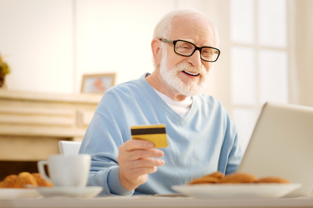 Make me smile. Delighted male person opening mouth and looking downwards while doing online shopping