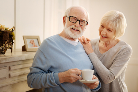 Love in age. Happy blonde female expressing positivity while embracing her husband and looking at him