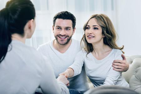 Gracias por la ayuda. Hermosa mujer encantada mirando a su terapeuta y agitando su mano mientras está sentado junto a su marido en el sofá