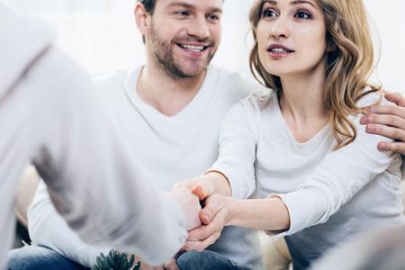 Blije patiënten. Vrolijke positieve jonge vrouwenzitting samen met haar echtgenoot en het uitdrukken van haar dankbaarheid aan haar therapeut terwijl het voelen van gelukkig