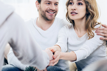 Glückliche Patienten. Nette positive junge Frau, die zusammen mit ihrem Ehemann sitzt und ihre Dankbarkeit ihrem Therapeuten beim Fühlen glücklich drückt