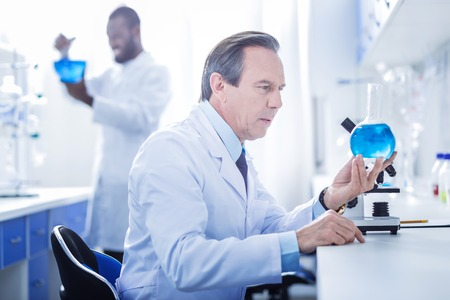 Chemical lab. Serious handsome smart scientist holding a flask and looking at the blue liquid in it while working in the chemical lab Stock Photo