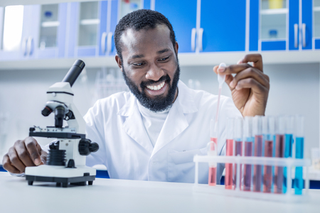 For analysis. Cheerful nice positive scientist in front of the microscope and taking a sample of liquid while doing biological analysis