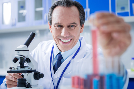 Modern lab. Delighted positive smart man wearing labcoat and working with test samples while being in the laboratory