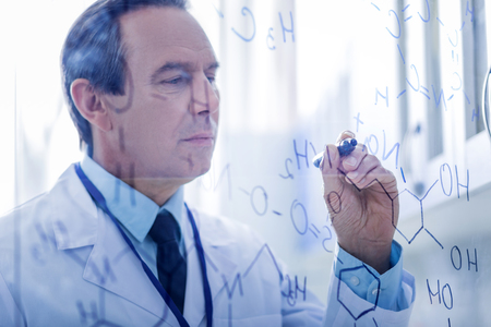 Theoretical analysis. Nice professional smart chemist holding a highlighter and looking at the chemical formulas while writing them