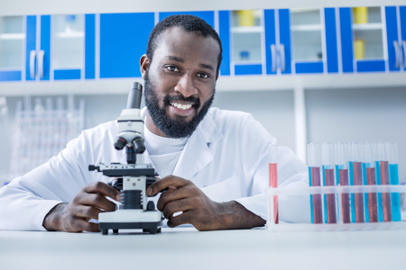 Favourite job. Happy handsome professional scientist sitting at the table and looking at you while being happy about his job Stock Photo