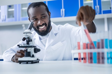 Chemical research. Positive smart nice chemist sitting at the table and taking a test tube while doing a chemical research
