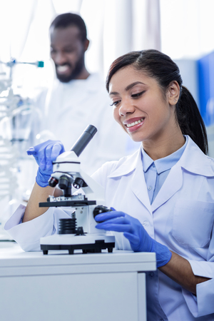 Intelligent scientist. Happy nice delighted woman smiling and using her microscope while enjoying her job Stock Photo