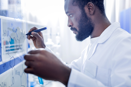 Chemical chain. Serious nice male scientist holding a highlighter and looking at the whiteboard while writing a formula