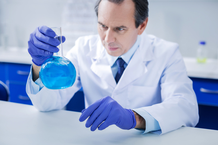 Chemical reagent. Selective focus of a glass flask being filled with blue liquid