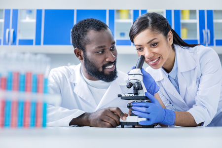 Our research. Delighted positive young woman using a microscope and smiling while doing a biological research with her colleague