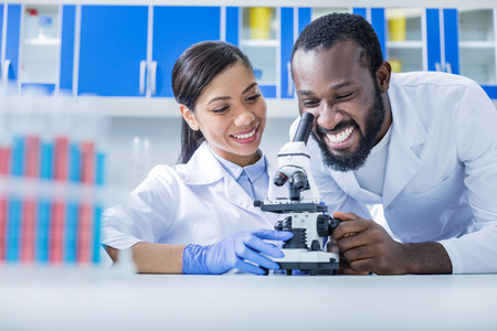 This is a success. Happy cheerful nice man sitting together with his colleague and looking into the microscope while doing a successful research