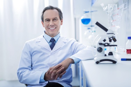 Healthcare system. Happy delighted nice doctor holding his hand together and smiling while looking at you