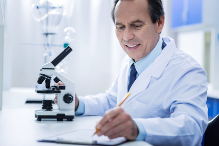 Professional notes. Cheerful positive professional scientist sitting at the table and writing an analysis while concluding his research Stock Photo