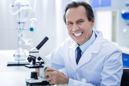 Microbiological studies. Happy smart professional biologist smiling and looking at you while working in the lab Stock Photo