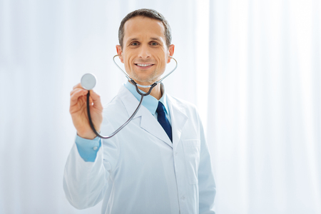 My gadget. Professional doctor keeping smile on his face and holding stethoscope while looking straight at camera