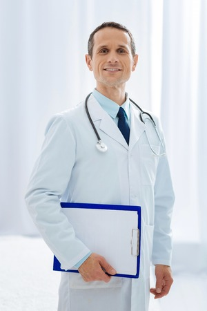 Visit me. Positive male person keeping smile on his face and holding folder in right hand while posing on camera